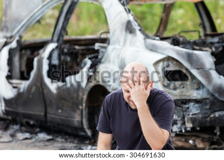 Crying upset caucasian man at road wreck accident or arson fire burnt wheel car vehicle junk - stock photo