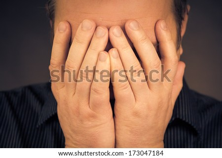 Crying white man with hands on face - stock photo