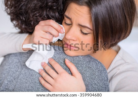 Crying woman is hugging her sister.  - stock photo