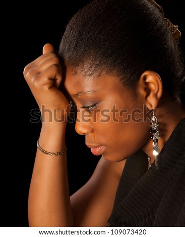 Crying young African Ghanese woman against a black background - stock photo