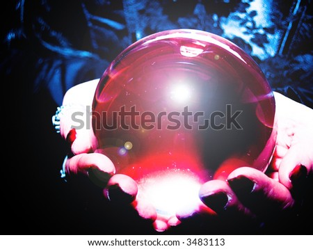 crystal ball glowing in hands - stock photo
