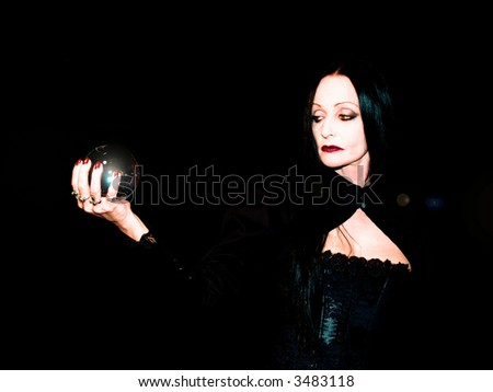 Crystal ball held in the hands of a fortune teller. - stock photo