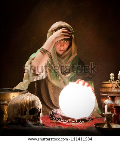 Crystal ball illuminating a young fortune telling gypsy - stock photo