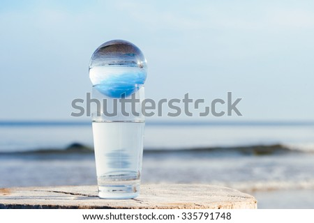 Crystal ball in a glass with water on the seashore - stock photo