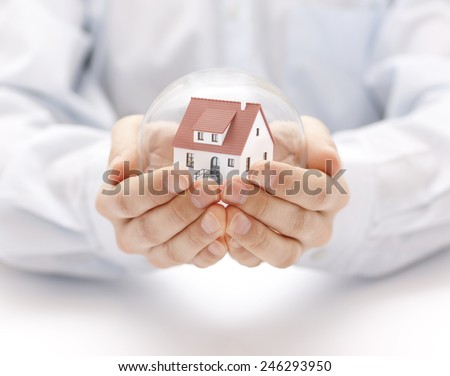 Crystal ball with house in hands - stock photo
