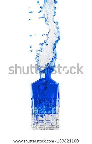 Crystal bottle with liquid splashing out on a white background - stock photo