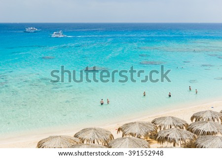 Crystal clear azure saltwater beach of Dubai with sunshader parasols - stock photo