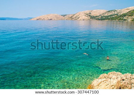 Crystal clear blue green Adriatic sea and a rocky beach on the island Krk, Croatia, with some tourists snorkeling and swimming, with other islands in the background - stock photo