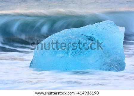Crystal clear blue iceberg melting between the waves