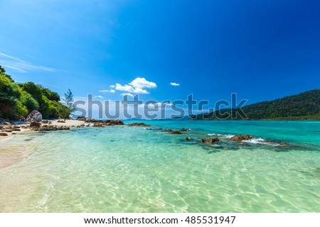 Crystal clear shallow water tropical beach with some foreground rocks at Ko Lipe mountain resort north overlooking Ko Adang island in a clear sunny day with deep blue sky C