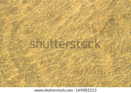 Crystal clear water on gold sand of sea