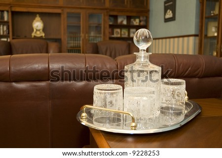 Crystal glass dishware in luxury room with sofa and old clock - stock photo