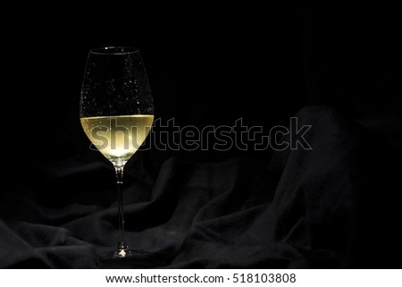 Crystal glass with white wine isolated over black background