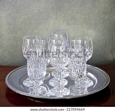 Crystal glasses ready for a celebration on a silver plate on a wooden table against a grunge background - stock photo