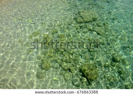 Crystal sea water and white sand and stones on the ocean floor.