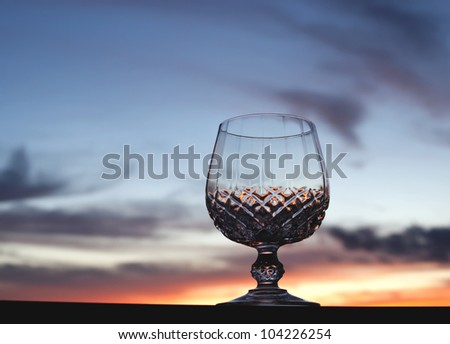 Crystal stem glass against beautiful sunset sky background with copy space. - stock photo