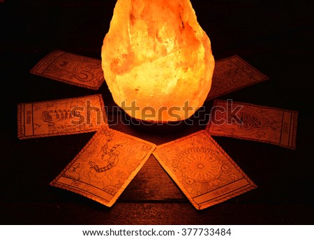 Crystal stone shining in the darkness and the tarot cards. Halloween and magic still life, fortune telling seance or black magic ritual with mysterious occult and esoteric symbols, divination rite  - stock photo