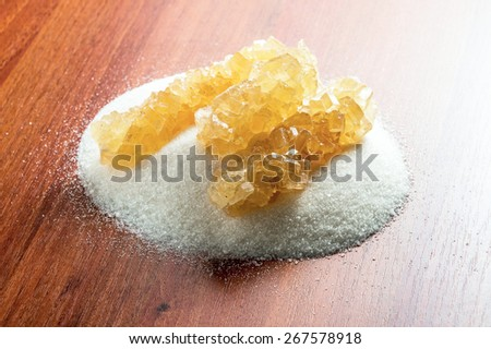 crystal sugar on a background of granulated sugar on the table - stock photo