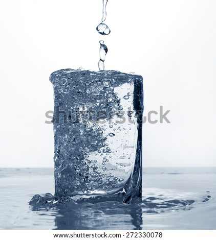 crystal water with many bubbles in a glass on white and blue background