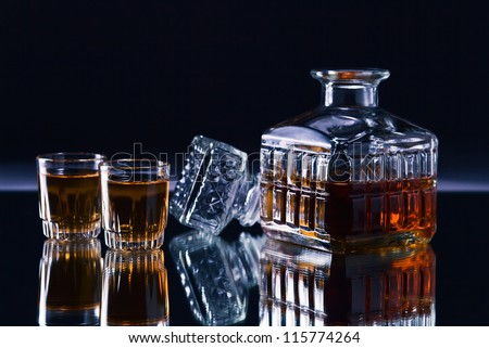 crystal whiskey decanter on a dark background - stock photo