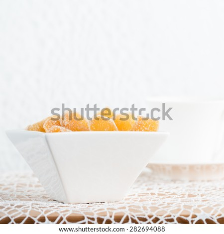 Crystallized ginger root  in white porcelain bowl and cup of tea on the background. Shallow DOF. Close-up photo, square - stock photo
