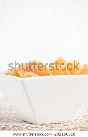 Crystallized ginger root  in white porcelain bowl. Bowl is cut vertically. Shallow DOF. Close-up photo, vertical - stock photo