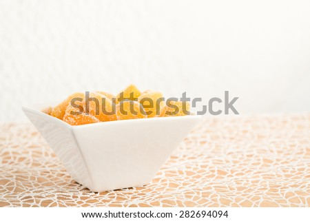 Crystallized ginger root  in white porcelain bowl on white tablecloth. Shallow DOF. Close-up photo, horizontal - stock photo