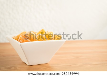 Crystallized ginger root  in white porcelain bowl on wooden background. Shallow DOF. Close-up photo, horizontal - stock photo