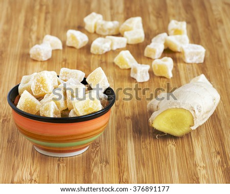 Crystallized pieces of ginger, grated ginger and ginger root on a wooden table.