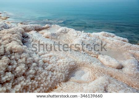 Crystallized salt cover the beach of Dead Sea. Jordan. - stock photo