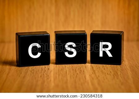 CSR or Corporate social responsibility text on black block - stock photo