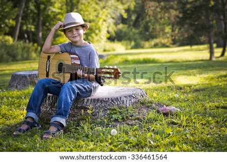 cuacasian boy with guitar in the park outdoors - stock photo