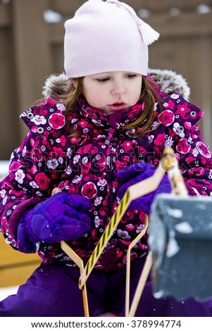 cuacasian female child is playing in the snow
