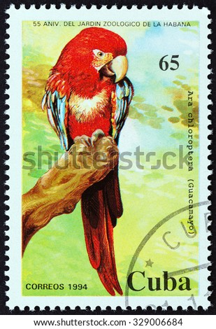 """CUBA - CIRCA 1994: A stamp printed in Cuba from the """"55th anniversary of Havana Zoo """" issue shows Green-winged Macaw (Ara Chloroptera), circa 1994.  - stock photo"""