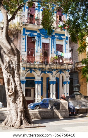 Cuba. Island. Havana. City. Old vintage retro house. Stone. Collapse. Destroyed. Wooden shutters instead of windows. Blue. white. drying laundry on balconies.  street is car and tree grows. Building.  - stock photo