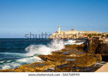 Cuba. Island. Ocean. Sea. Green and brown stones. High lighthouse. Waves breaking on the shore. White water spray. Blue sky. Nature - stock photo