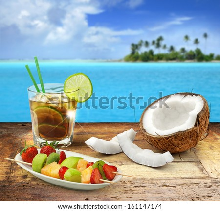 cuba libre and tropical fruit on a wooden table in a polynesian seascape - stock photo