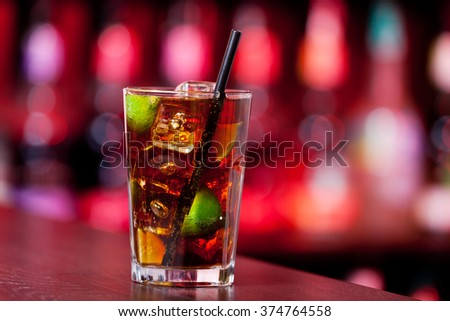 Cuba libre cocktail on a bar counter in a night club. Blurred bottles on background - stock photo