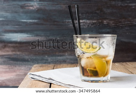Cuba libre cocktail on the rustic background - stock photo