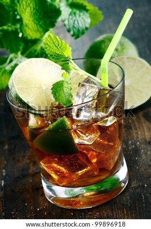 Cuba Libre Drink with lime and Cola,on a wooden plate - stock photo