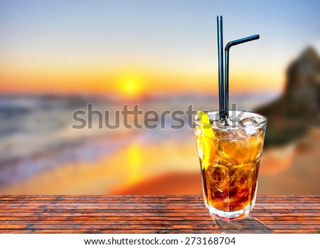 Cuba libre exotic tasty cocktail with beautiful sunset background - stock photo
