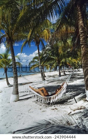 CUBA, Maria La Gorda, coconut palm trees and woman relaxing on the beach - FILM SCAN - stock photo