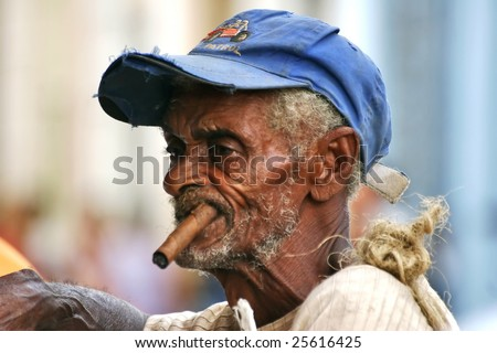 CUBA - OCTOBER 25: Picturesque Cuban old man is on one of the streets of Trinidad on October 25, 2005 in Cuba. Cuba is famous of its cigars. - stock photo