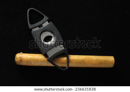 Cuban Brown Havan Cigar and Cutter on a black background - stock photo