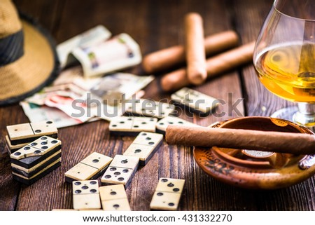 cuban cigar and domino on table, from overhead