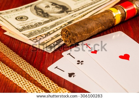 Cuban cigar and golden chain with playing cards and money on the table mahogany. Focus on the cuban cigar, identification cards ace Russian letter