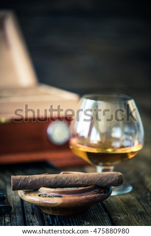 cuban cigar and wooden humidor in background