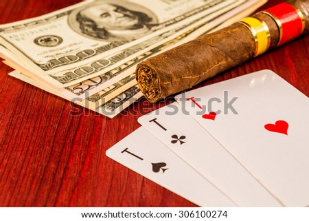 Cuban cigar with playing cards and money on the table mahogany. Focus on the cuban cigar, identification cards ace Russian letter
