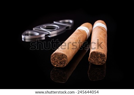 Cuban cigars and cutter isolated on black background - stock photo