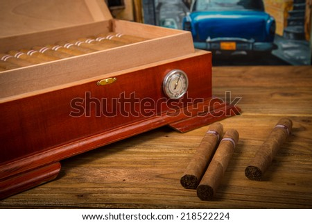 Cuban cigars and humidor on rustic wooden table with Cuban painting of american old car in background